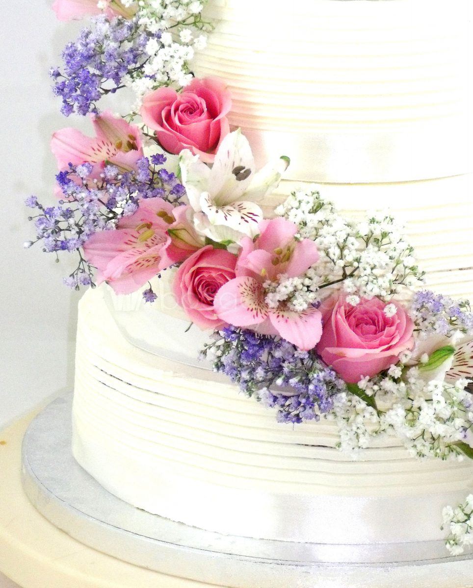Tarta cubierta de buttercream blanco decorada con flores naturales.