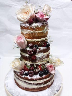 Tarta desnuda de tres pisos decorada con frutos rojos y flores naturales.