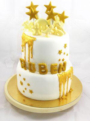 Tarta de dos pisos forrados en fondant blanco, decoracion de estrellas y nombre del niño en fondon dorado, chocolate fundido en color dorado y chocolatinas con forma de muñeco en chocolate blanco.