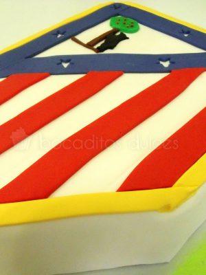 Tarta tallada con la forma del escudo del atlético de Madrid.