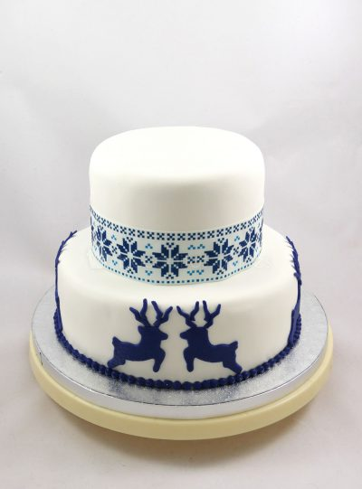 Tarta de dos pisos, cubiertos de fondant blanco, decorada con renos de fondant azul y papel de azucar con motivos nórdicos.
