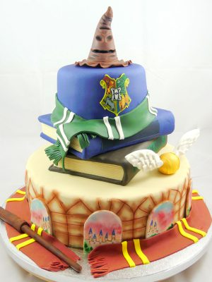 Tarta de tres pisos decorados cada piso con decoracion en tematica Harry Potter.