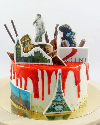 Tarta cubierta de buttercream blanca con chocolate rojo fundido, decorado con diferentes monumentos del mundo en papel de azúcar.