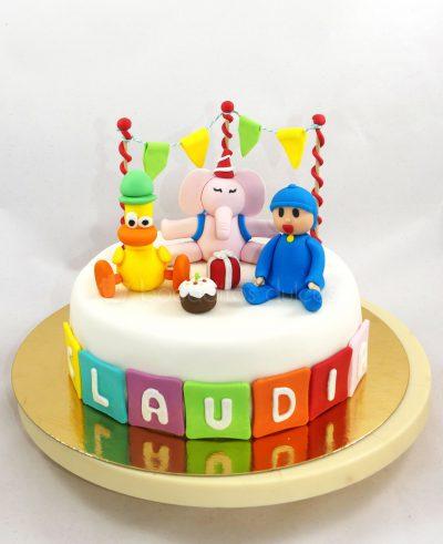 Tarta cubierta de fondant blanco, con el nombre de Claudia en cuadrados de colores de fondant, personaje de Pato en fondant, personaje de Eli en fondant, y el personaje principal de la serie Pocoyo