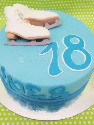 Tarta sencilla forrada con fondant azul, nombre y años del cumpleañero y decorada con dos patines para el hielo modelados en fondant.
