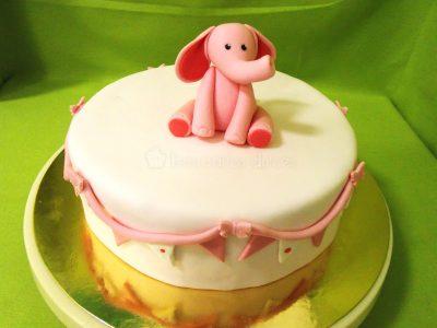 Tarta cubierta de fondant blanco, banderines y cuerda de fondant color rosa alrededor y elefante de fondant rosa decorando su base.
