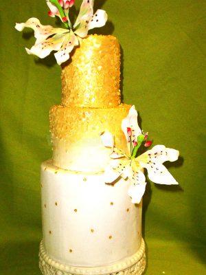 Tarta de tres pisos decorada con lentejuelas de color oro y dos flores en fondant.