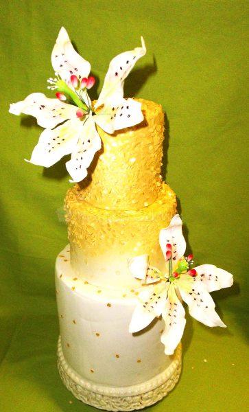Tarta de tres pisos decorada con lentejuelas en color oro y dos flores de fondant.