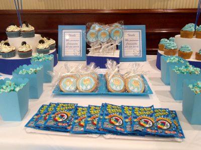 Mesa dulce en color azul, compuesta por cupcakes con buttercream de color azul sabor vailnilla, cajitas de palomitas de color azul, galletas redondas con palo, decoradas con papel comestible de azucar, galletas de mantequilla redondan decoradas con papel comestible de azúcar, bolsitas de chuches, y macarons de color blanco.