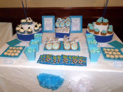 Mesa dulce en color azul, compuesta por cupcakes con buttercream de color azul sabor vailnilla, cajitas de palomitas de color azul, galletas redondas con palo, decoradas con papel comestible de azucar, galletas de mantequilla redondan decoradas con papel comestible de azúcar, bolsitas de chuches, y macarons de color blanco