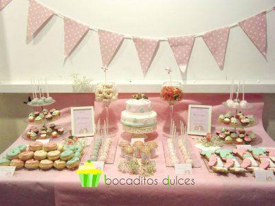 Mesa dulce decorada con tonos pastel, compuesta por Cake pops cubiertos con candy mels en tonos verde y rosa decorados con bolitas de caramelo en color blanco. Galletas de mantequilla con motivos de bebe decorados con fondant de color verde, rosa, y blanco. Tarros de cristas rellenos de chuherias, donuts con glaseado de color verde y rosa decorados con bolitas de caramelo color blanco, y tarta de dos pisos cubierta de fondant blanco el prier piso y fondant rosa el segundo, decorados los dos pisos con lunares de distintos tamaños de color rosa y verde y en la base un osito de fondant de color marron tumbado encima de una mantita.