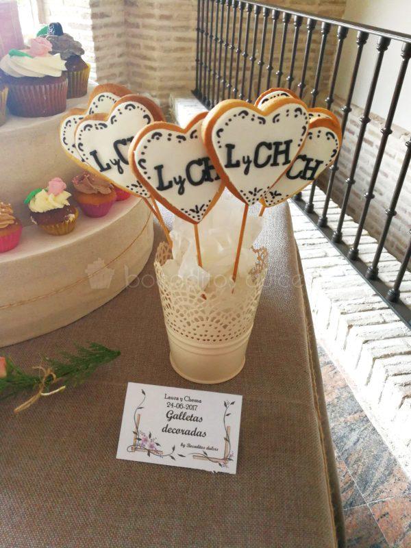 Galletas de mantequilla en forma de corazon con palo, decoradas con fondant blanco y las iniciales de los novios en esta ocasion.
