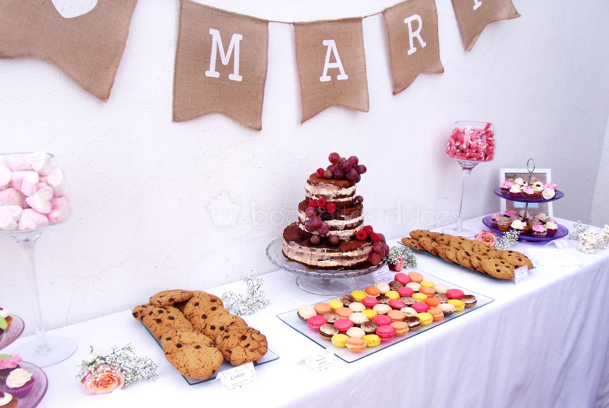 Mesa dulce de estilo rustico compuesta por minicupcakes de distintos sabores, galletas con chips de chocolate, macarons de distintos sabores y tarta de desnuda de tres pisos decorada con frutas del bosque.