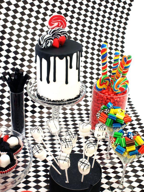 Mesa dulce compuesta de tarta dirp cakes cubierta de buttercream blanca y chocolate derretidos chorreando, decorada con piruletas y fresas naturales,y diferentes tipos de gominolas.s