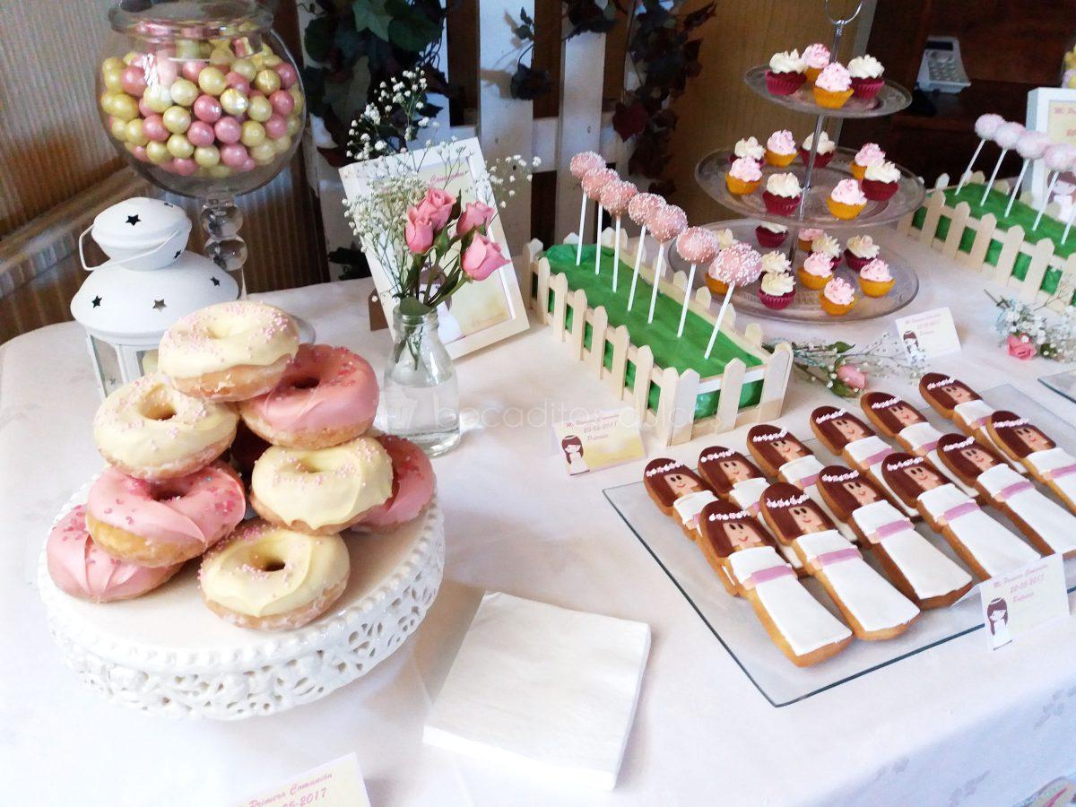 Mesa dulce compuesta de tarritos de cristal con batido de fresa, distintos tipos de golosinas, cake pops cubiertos de candy mels blanco y rosa decorados con bolitas de caramelos de color rosa y blanco, chocolatinas individiales, mini cupcakes de fresa y chocolate blanco, galletas de mantequilla con forma de niña de comunion decoradas con fondant, y donuts con graseado de color blanco y rosa.