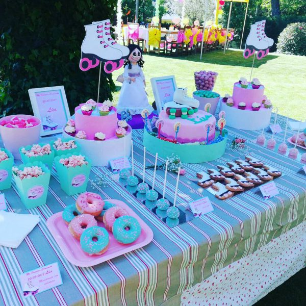 Mesa dulce en colores rosa y verde compuesta por donuts con glaseado en color rosa y verde y decorados con bolitas de caramelos de distintos colores, minicupcakes con buttercread de fresa y chocolate blanco, cakepops cubiertos de candy mels rosa y azul, con bolitas de caramelos de colres,galletas de mantequilla con forma de patin, distintios tipos de gominolas, cajitas de palomitas y para terminar una tarta cubierta de fondant rosa, con dos patines de fondon como adorno. .