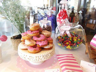 Mesa dulce de estilo vintage en colores rosos y blancos, con donuts con glaseado blanco y rosa, cakepops cubiertos con candy mels blanco y rosa y pequeños cristalitos de caramelo en color rosa, ninicupcakes con buttercream de fresa y vainilla, botellas de cristal con batido de fresa y pequeños paquetes de palomitas.