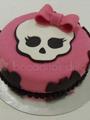Tarta cubierta de fondant rosas, con murcielagos alrededor en fondant negro y calabera en fondant blanco y lazo tambien de fondante color rosa.