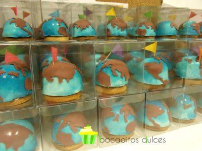 Mini tartar cubiertas de fondant azul decoradas con fondant simulando los continentes en color marron y banderines de colores