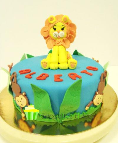 tarta cubierta en fondant azul, con monos decorativos alrededor de la tarta de fondant, hojas en fondant de color verde, el nombre de alberto en color rojo de fondant, y un pequeño leon de fondant