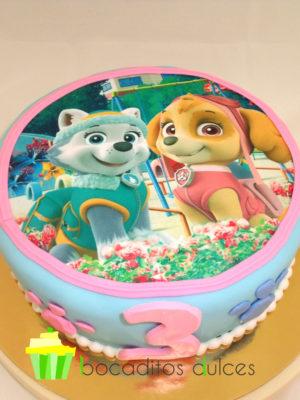 Tarta cubierta de fondant azul con pequeñas huellas de cachorro de fondant alrededor de la tarta, con una foto de los protagnistas de la serie en papel de azúcar.