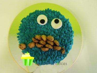 Tarta cubierta de buttercream de vainilla de color azul, decorada con unos ojos de fondant y galletas.