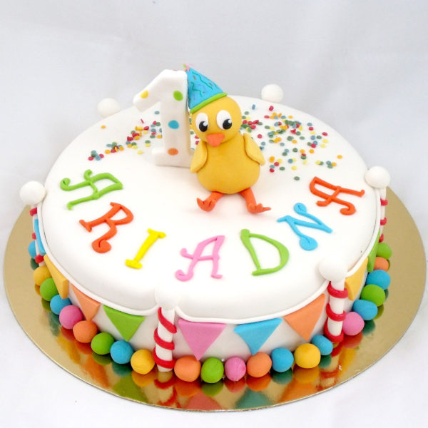 tarta cubierta de fondant blanco con decoraciones en bolitas de fondant de colores alrededor y pequeños triangulos de colores el numero uno en fondant blanco el nombre de Ariadna en fondant de colores, confetis de caramelo y un pollito amarillo en fondant