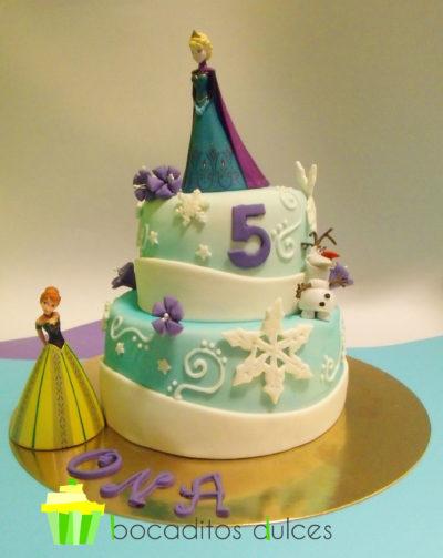 Tarta de dos pisos cubierta de fondant blanco y pintada ligeramente en color azul con tinta comestible, adornada con copos de nieve en fondant blanco y pequeñas flores moradas de fondant, el muñeco olaf en fondant y las dos princesas portagonistas en muñecas de platico.
