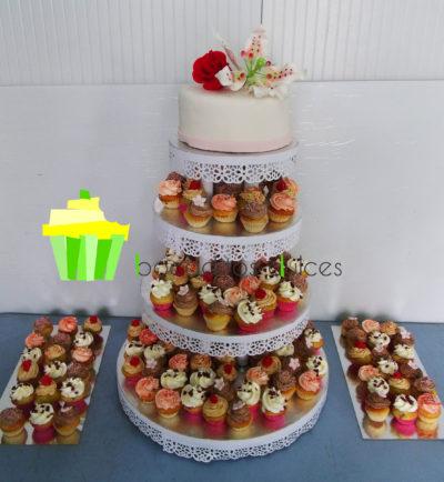 Torre de cuatro pisos compuesta de tarta cubierta de fondant blanco y decoradas con folres de fondant, variesad de ninicupcakes decorados con buttercream de distintos sabores y pequeñas flores de fondant
