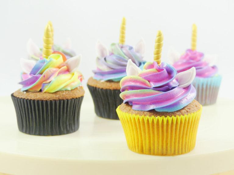 Cupcakes de vainilla, decorados con butterceam multicolor de vainilla y decorados con unas pequeñas orejas de color blanco y un pequeño cuerno dorado de fondant.