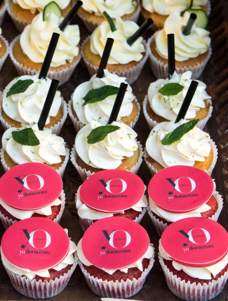 """Cupcakes red velvet, decorados con buttercream de vainilla y el logotipo de la empresa """"Yo dona""""en papel de azúcar, cupcakes de vainilla con buttercream sabar mojito decorados pajita, y una hoja de hierbabuena"""