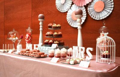 Variedad de gominolas, vasitos con vizcocho de red velvet, buttercram de fresa y nata, cupcakes de chocolate con buttercream de fresa y dulce de leche, macrons, cukepops bañados en cany mels de color blanco y rosa.