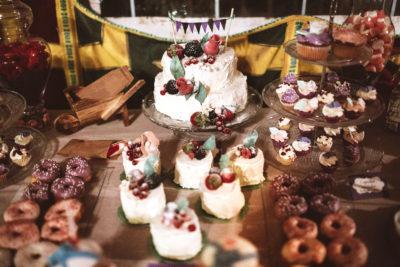 Mesa dulce compuesta por cake pops bañados en candy mel de color morado y blanco, ninipastelitos, donuts con distinto tipo de glaseado, mini cupcakes y cupcakes de bizcocho de vainilla cubiertos de buttercream de mora, fresa, y vainilla,minivasos rellenos de bizcocho de vainilla , buttercream de vainilla y mermelada de fresa, trata de dos pisos cubierta con buttercream de vainilla y decorada con frutos rojos