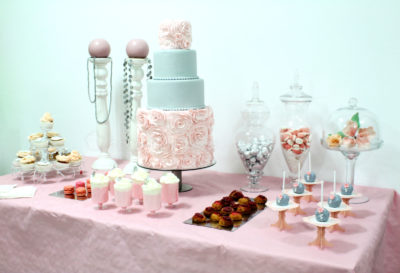 Mesa compuesta por cake pops, variesad de gominolas, nini pastelitos, vasitos con batidos de fresa y nata, macarons, cupcakes y tarta personalizada de cuatrao pisos