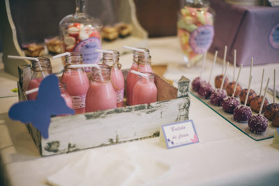 Cake pops cubiertos de candy mels de color morado y naranja decorados con bolitas blancas y moradas, botellas rellenas de batido de fresa y variedad de gominolas