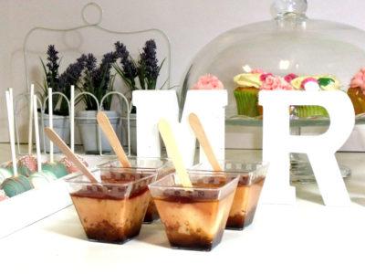 Vasitos de plastico rellenas de diferentes dulces y cake pops decorados con glaseado de color banco, azul y rosa con bolitas blancas.