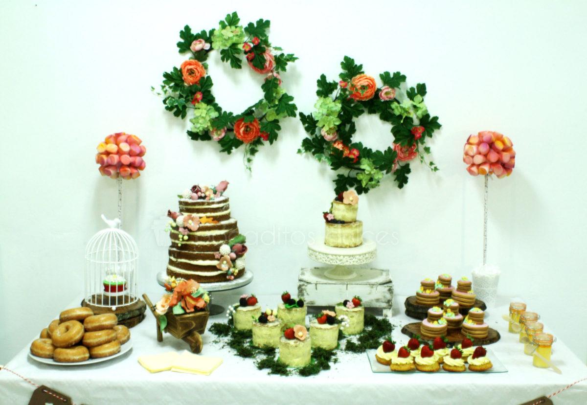 Mesa dulce compuesta por nubes de gominola, nini vasos de bizcocho y buttercream, pastelitos , galletas de mantequilla, donuts, tarta desnuda de tres pisos decorada con furtas del bosque y tarta semidesnuda, decorada con flores de fondant