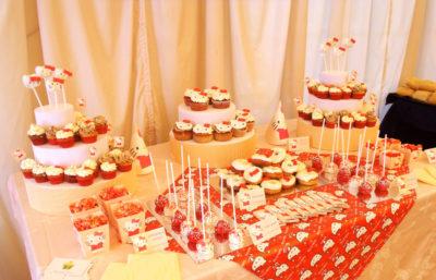 Mesa compuesta por cake pops, cup cake y mini cupcakes, distintos tipos de gominola, cake pops, donuts, chocolatinas y palomitas.