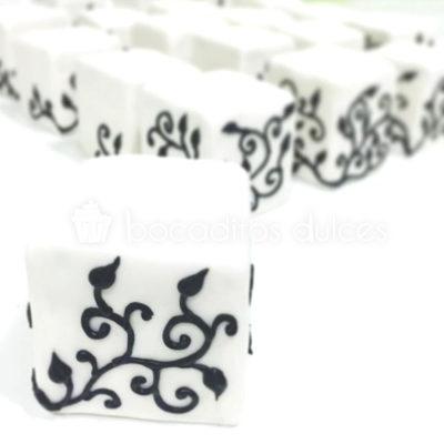 minitartas terminadas en fondant con detalles en glasa real. negro sobre blanco.