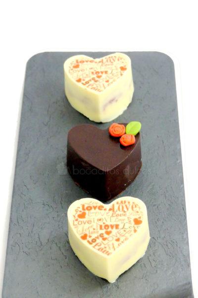 Pequeños pastelitos de frutas, cubiertos con chocolate blanco y con leche, decorados con letras de papel de azúacar, y pequeñas flores de fondant