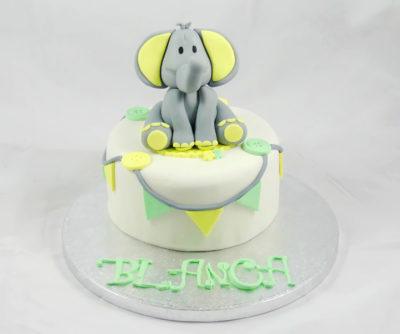 Tarta cubierta de fondant blanco, con pequeños triangulos de color amarillo y verde en fondant, botones en fondant de color verde y amarillo, y un pequeño elefante en fondant.