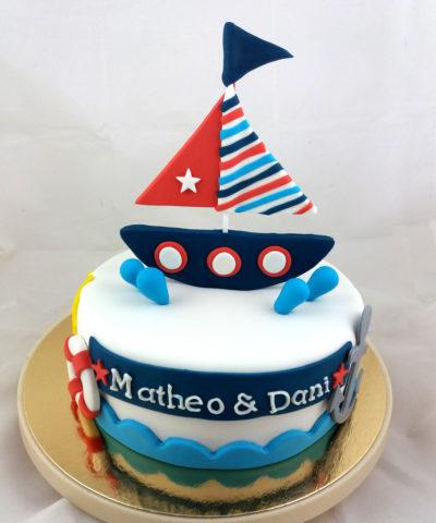 Tarta cubierta de fondant blanco, con una pequeña anacla de fondant, y flotador tambien en fondant, el nombre de Matheo y Dani en fondant blanco, pequeñas gotas de fondant azul y un gracios barco en fondant sobre la tarta.
