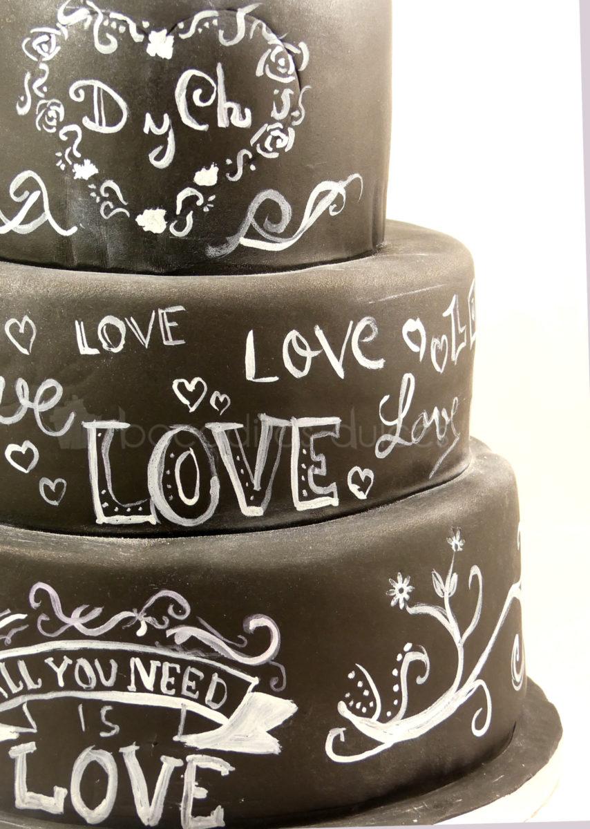 Tarta de tres pisos cubierta de fondant negro, y decorada con dibujos y tetras con tinta blanca comestible.