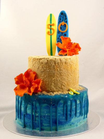 Trata de dos pisos, el de la base cubierto de buttercream azul y ganache chorreando alrededor, y la segunda cubierta de buttercream con galleta y decorada con dos tablas de surf de fondant y flores de fondant color naranja.