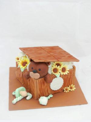 Tarta cuadrada forrada de fondant simulando tablas de madera, pequeñas flores amarillas de fondant, pequeño sonajero de fondant, chupete tambien de fondant, y osito tambien de fondant