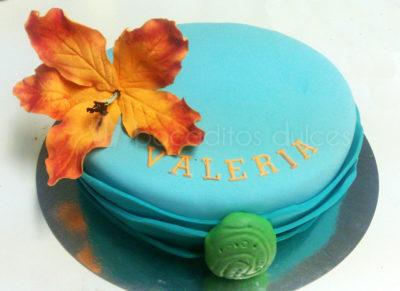 Tarta cubierta de fondant azul, con flor de color naranja de fondant nombre de Valeria en color naranja en fondant y colgante de la pelicula en fondant verde.
