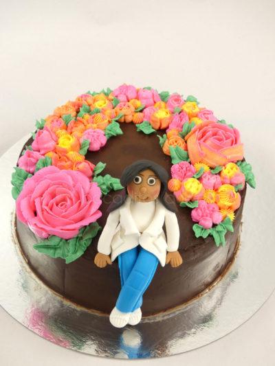 Tarta cubierta de ganache de chocolate, decorada con flores de buttercream de colores y muñeca personalizada en fondant