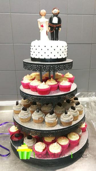 Torre de dulces compuesta por una tarta forrada en fondant blanco, con pequeñas bolitas negras de fondant alrededor de la tarta, con dos muñecos vestidos de novios coronando la tarta, cupcakes de diferentes sabores.
