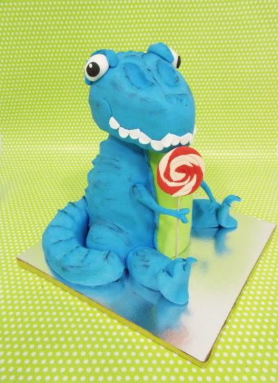 Tarta tallada con la forma de un dinosaurio, y despues forradas con fondant de color azul, y detalles en fondant como los ojos, dientes, y una pequeña piruleta.