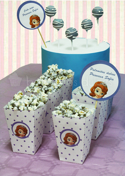 Mesa dulce compuesta por cake pops cubiertos de candy mels azul y chocolate blanco fundido, cajitas personalizadas con palomitas, cupcakes de vainilla, galletas de mantequilla con forma de coroza cubiertas de fondant , brochetas de chuches, y bolas de chicle.